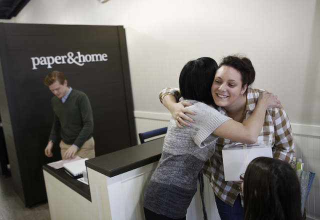 Brooke Coxen hugs customer Kayla Geraci, right, at paper & home in Las Vegas Tuesday, Nov. 19, 2013