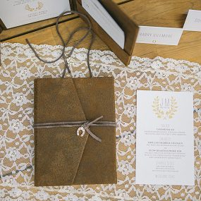rustic barn wedding invitations with leather pocket and horseshoe charm